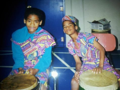 A young Douglas-Ferreira and his sibling celebrate Kwanzaa with an African drum and dance.