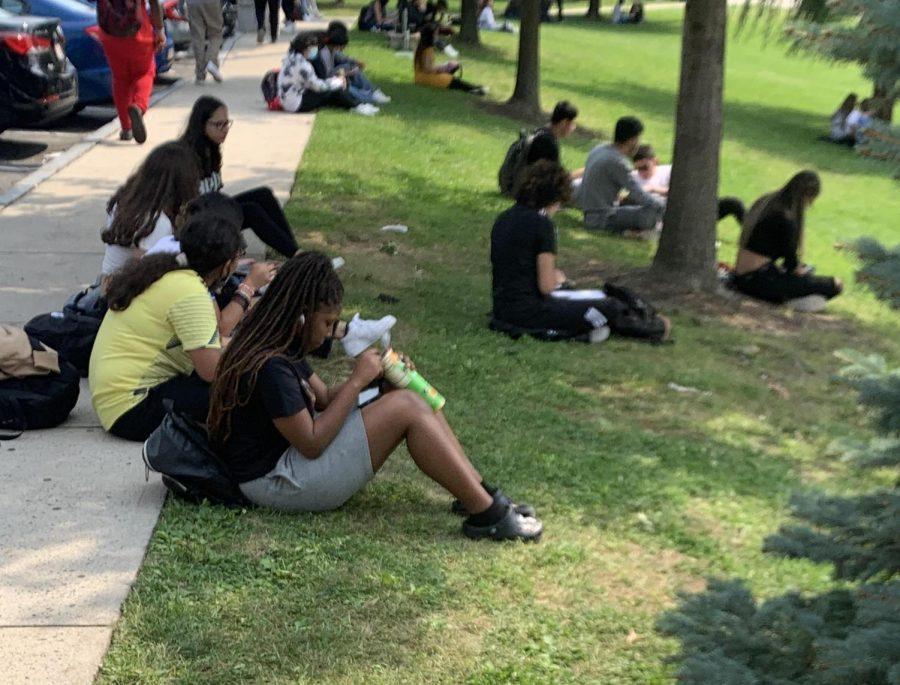 Students enjoy the fresh air, mask break, and each others company as they eat lunch on the grass under the trees.